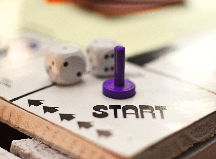 purple pardot game piece on wooden game board